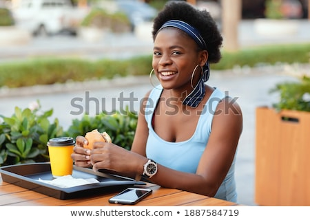 Woman drinking coffee while sitting by glass table Stock photo © wavebreak_media
