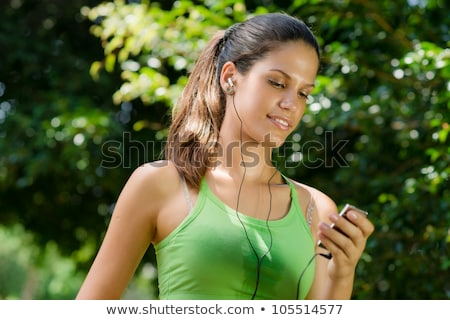 Image of brunette woman running and listening to music with earphones Stock photo © deandrobot