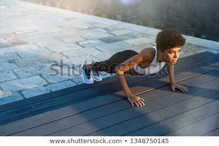 Young athletic woman doing push ups outdoors in urban city background Stock photo © GVS