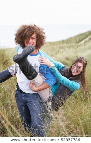 Teenage Couple Having Piggy Back Ride In Sand Dunes Stock photo © monkey_business