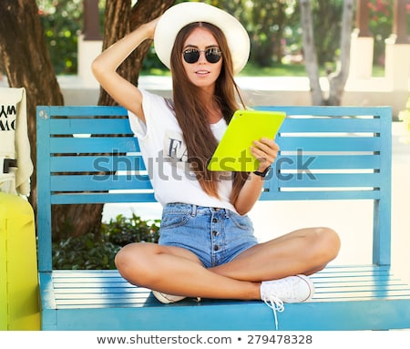Tanned casual young woman relaxing with a tablet Stock photo © dash