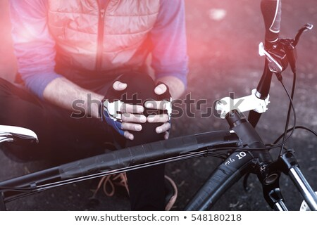 Foto stock: Midsection of male biker in pain holding his injured leg