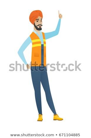 Jonge bouwer wijzend wijsvinger omhoog Stockfoto © RAStudio