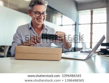 smiling man taking smartphone out parcel box Stock photo © dolgachov