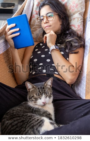 Young brunette girl holding glasses in her hand. Cat glasses. The hair is gathered in a bun. Stock photo © Traimak