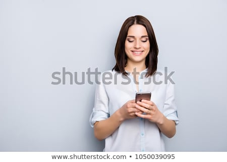 pretty young businesswoman using mobile phone and holding file stock photo © boggy