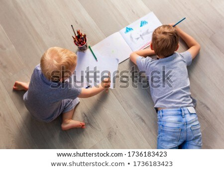 Preschool boys drawing on floor on paper, playing with educational toys - blocks, train, railroad, v Stock photo © Len44ik