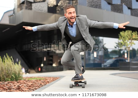 The young handsome businessman with longboard in the office  Stock photo © Elnur