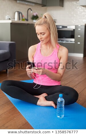 Cute woman sitting on yoga mat and browsing mobile phone for songs Stock photo © dash