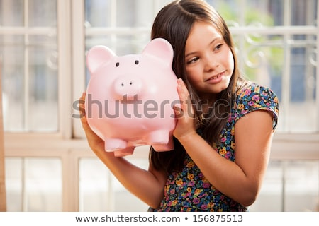 smiling little girl with piggy bank and money at home stock photo © lopolo
