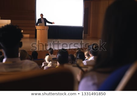 front view of mixed race businessman standing on podium with diverse colleagues while speaking at bu stock photo © wavebreak_media