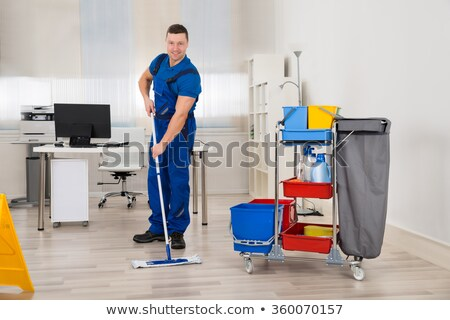 Happy Male Janitor Mopping Floor In Office Stock photo © AndreyPopov