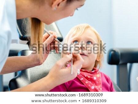 Dentist explaining treatment to a child using a plush toy Stock photo © Kzenon