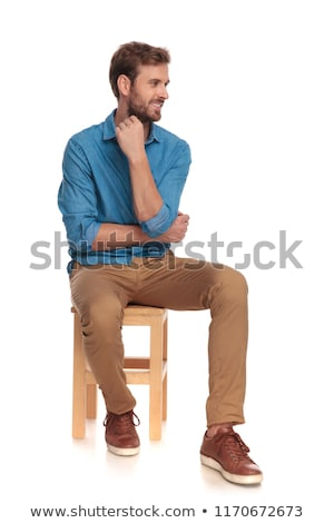 young smart casual man sitting and looking to side stock photo © feedough