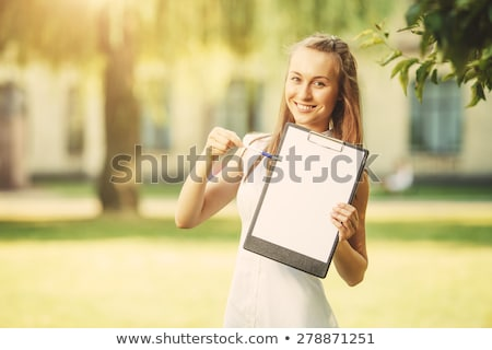 smiling young casual student holding clipboard stock photo © feedough