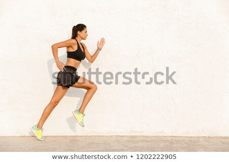 Full length image of caucasian woman 20s in sportswear working o Stock photo © deandrobot