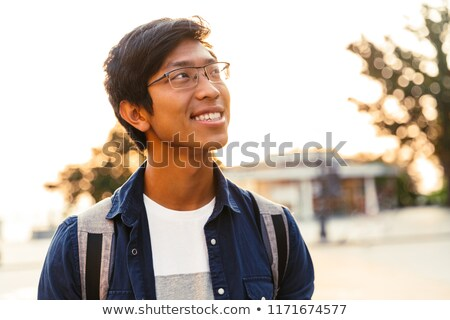 Picture of Cheerful asian male student in eyeglasses looking away Stock photo © deandrobot