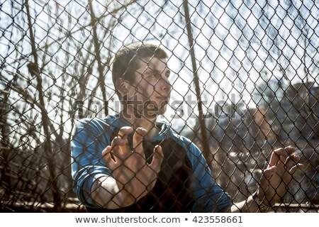 Mann außerhalb schließen Zaun Gefühl Hände Stock foto © Lopolo