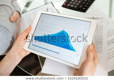 Blue financial graph on display of touchpad held by analyst or financier Stock photo © pressmaster
