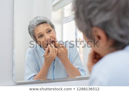 Senior vrouw schoonmaken tanden flosdraad tandheelkundige zorg Stockfoto © dolgachov