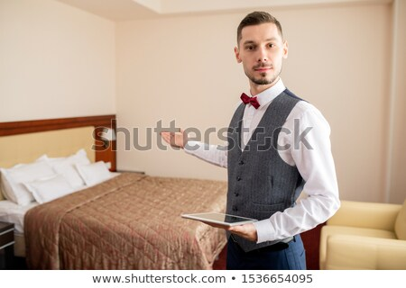 young professional in elegant clothes holding touchpad and pointing at bed stock photo © pressmaster