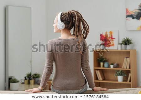 Back view of young restful female in activewear and headphones sitting on sofa Stock photo © pressmaster