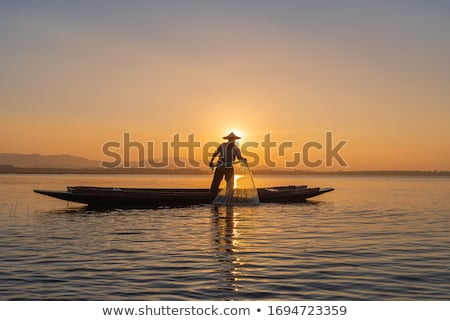 Fisherman fishes in the sea at sunset Stock photo © galitskaya