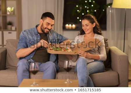 couple with red wine eating takeaway pizza at home Stock photo © dolgachov