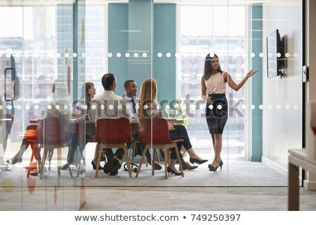 vista · lateral · jóvenes · hombre · de · negocios · mirando · vidrio · ventana - foto stock © HASLOO