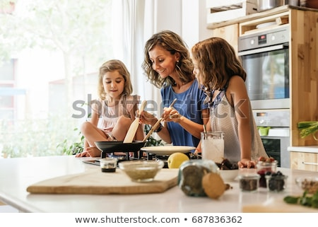 Woman cooking crepes with her daughters Stock photo © photography33