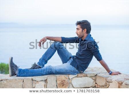Fiatalember élvezi tenger szellő áll kő Stock fotó © Kotenko