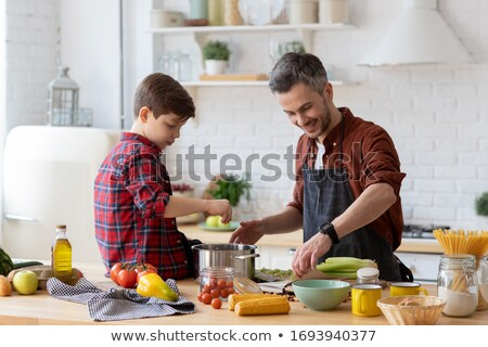 Man preparing a meal with the help of a cookbook Stock photo © photography33