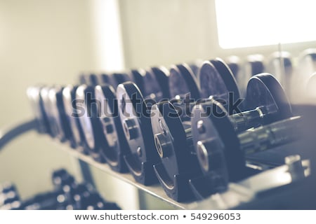 black and white image of a rack of dumbbells at a gym stock photo © pixelsnap