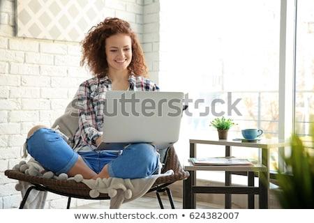 beautiful women smiling using the laptop stock photo © deandrobot