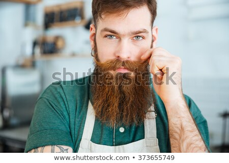 Barista with beard and moustache standing in coffee shop Stock photo © deandrobot