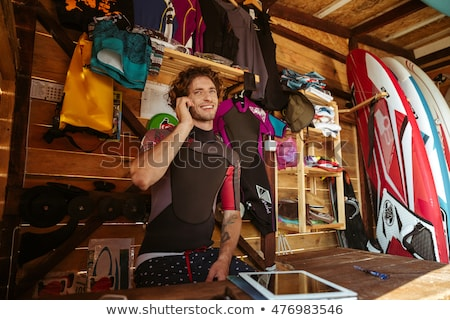 man in swimsuit using smartphone in the surf shack stock photo © deandrobot