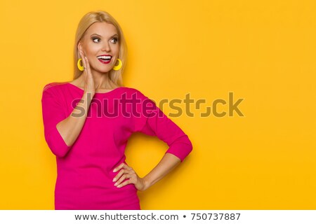 smiling blonde woman standing with hands on waist stock photo © feedough