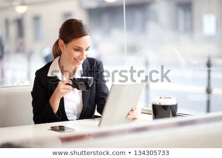 Smiling young businesswoman holding tablet and drinking coffee Stock photo © deandrobot