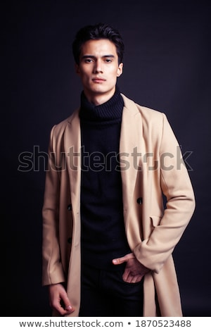 cool real young man in coat on black background posing Stock photo © iordani