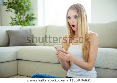 shocked young lady sitting on floor near sofa indoors stock photo © deandrobot