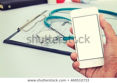 Stockfoto: Doctor Using Smartphone App In Hospital Office