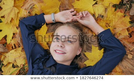 family lying in autumn leaves in a park stock photo © is2