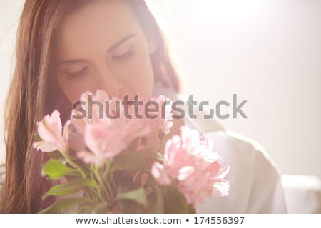 close up of woman smelling flowers stock photo © is2