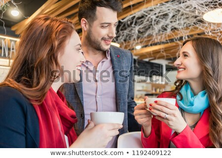 Attractive young woman meeting an old friend while enjoying a hot drink Stock photo © Kzenon