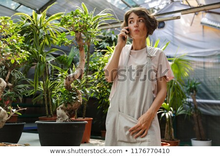 Surprised woman gardener standing over plants in greenhouse talking by mobile phone. Stock photo © deandrobot