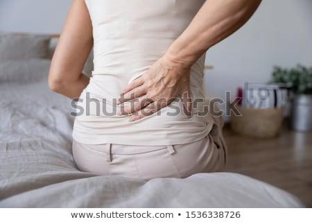 mujer · sufrimiento · dolor · de · espalda · sesión · cama · casa - foto stock © andreypopov