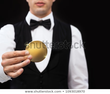 close up of magician with golden coin over black Stock photo © dolgachov