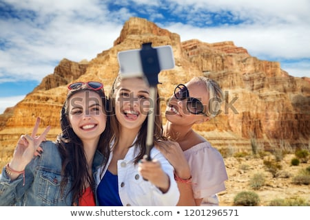 friends taking selfie by monopod at grand canyon stock photo © dolgachov
