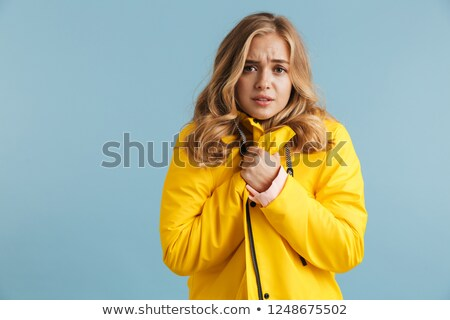 Stockfoto: Image Of Frozen Woman 20s Wearing Yellow Raincoat Holding Arms A