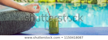 Closeup of a woman's hands during meditation with a green smoothies of spinach, orange and banana on Stock photo © galitskaya